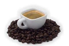 Espressocup mit den Kaffeebohnen getrennt auf Weiß Lizenzfreie Stockfotos