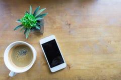 Espressokaffe i den vita koppen med smartphonen med kopieringsutrymme Arkivbilder