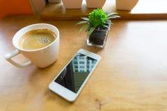 Espressokaffe i den vita koppen med smartphonen med kopieringsutrymme Arkivfoto