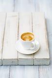 Espressokaffe i den vita koppen på den gamla lantliga stiltabellen arkivbilder