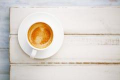 Espressokaffe i den vita koppen på den gamla lantliga stiltabellen royaltyfri fotografi