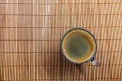 Espressokaffe med den guld- bot-bubblade cremaen som ses från ovannämnt i en kristallklar kopp på bambuplattahållare royaltyfri fotografi