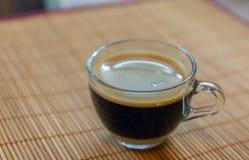 Espressokaffe med den guld- bot-bubblade cremaen som ses från ovannämnt i en kristallklar kopp på bambuplattahållare arkivbild
