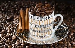 Espressokaffekopp i en miljö av stekte kaffekorn Fotografering för Bildbyråer