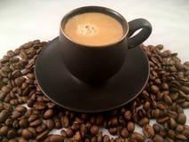Espressokopp- och kaffebönor Arkivfoto