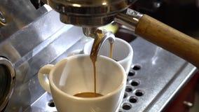 Espressomaskin som häller nytt kaffe in i en keramisk kopp arkivfilmer