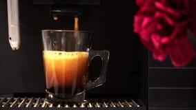 Espressomaskin som häller nytt kaffe in i exponeringsglaskoppen arkivfilmer