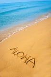 Esprima Aloha scritto in sabbioso sulla spiaggia tropicale Immagini Stock Libere da Diritti