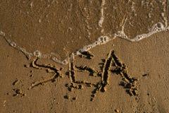 Esprima il mare scritto sulla sabbia lavata dalle onde Fotografie Stock