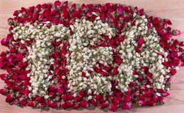 Esprima il tè fatto dei germogli di fiore secchi del gelsomino sopra il mucchio dei germogli della rosa rossa Fotografie Stock Libere da Diritti