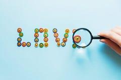 Esprima l'amore dalla raccolta dei perni dei bottoni multicolori della cancelleria nell'ambito del tema di amore della lente, fin Immagine Stock