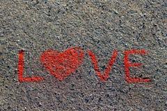 Esprima l'AMORE scritto sull'asfalto, terra Colore rosso di gesso Fotografia Stock