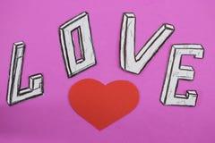 Esprima l'amore sul fondo rosa del fondo con cuore e gli anelli di fidanzamento fotografie stock libere da diritti