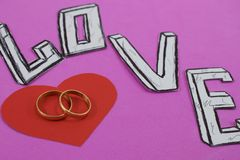 Esprima l'amore sul fondo rosa del fondo con cuore e gli anelli di fidanzamento fotografia stock libera da diritti