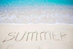 Esprima l'estate scritta a mano sulla spiaggia sabbiosa con l'onda di oceano molle su fondo Fotografia Stock
