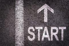 Esprima l'inizio e una freccia scritta su una strada asfaltata Immagine Stock