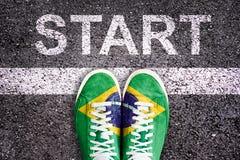 Esprima l'inizio scritto su una strada asfaltata con le gambe e le scarpe colorate con la bandiera brasiliana Immagine Stock Libera da Diritti