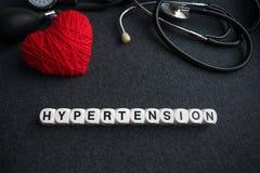 Esprima l'ipertensione del cuore dai cubi bianchi con le lettere sulle sedere scure Immagine Stock