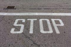 Esprima la fermata scritta su una strada asfaltata, il fanale di arresto Immagini Stock Libere da Diritti