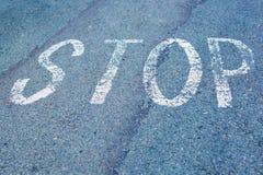 Esprima la fermata scritta su una strada asfaltata, vista superiore sulla strada nella prospettiva Fotografia Stock