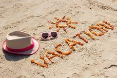 Esprima la vacanza con forma degli occhiali da sole del sole e del cappello di paglia sulla sabbia alla spiaggia Fotografie Stock