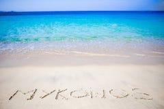 Esprima Mykonos scritto a mano sulla spiaggia sabbiosa con l'onda di oceano molle su fondo Fotografia Stock