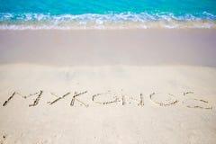 Esprima Mykonos scritto a mano sulla spiaggia sabbiosa con l'onda di oceano molle su fondo Fotografie Stock