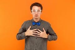 Esprimendo professore che esamina macchina fotografica, tenendo cuore e lookin Fotografia Stock