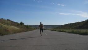 Esprintar al hombre del corredor que activa en la carretera Entrenamiento masculino del atleta del deporte al aire libre en el ve almacen de video