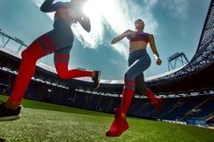 Esprinter atlético fuerte de la mujer, corriendo en el estadio que lleva en ropa de deportes Motivación de la aptitud y del depor imagenes de archivo
