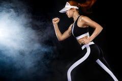 Esprinter atlético fuerte de la mujer, corriendo en el fondo negro que lleva en ropa de deportes Motivación de la aptitud y del d imagen de archivo