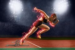 Esprinter de la mujer que deja bloques el comenzar en la pista atlética imagenes de archivo