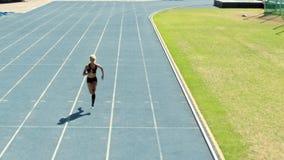 Esprinter que practica en circuito de carreras atlético almacen de metraje de vídeo