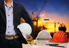 Esprit d'homme d'ingénieur ; casque de sécurité blanc de h se tenant contre le travail Images stock