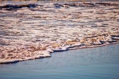 Espuma, areia na praia imagens de stock