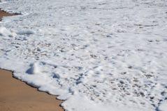 Espuma blanca de la onda en la arena Fondo Imágenes de archivo libres de regalías