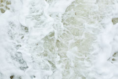 A espuma branca causou a pela ação da onda Fotografia de Stock