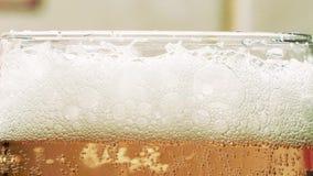 Espuma a cerveja em um fim de vidro do cálice acima filme