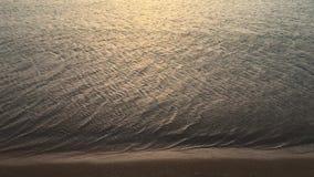 A espuma da onda em ondas espumosas de um Sandy Beach rola sobre a textura arenosa da praia video estoque
