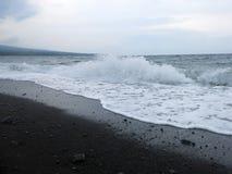 Espuma das ondas, da ressaca e do mar que bate a praia vulc?nica preta arenosa da areia de Bali Em Amed, o mar ? quieto, mas as o fotos de stock