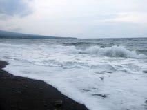 Espuma das ondas, da ressaca e do mar que bate a praia vulc?nica preta arenosa da areia de Bali Em Amed, o mar ? quieto, mas as o imagens de stock royalty free