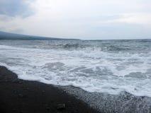Espuma das ondas, da ressaca e do mar que bate a praia vulc?nica preta arenosa da areia de Bali Em Amed, o mar ? quieto, mas as o fotografia de stock royalty free