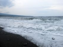 Espuma das ondas, da ressaca e do mar que bate a praia vulc?nica preta arenosa da areia de Bali Em Amed, o mar ? quieto, mas as o fotografia de stock