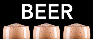 Espuma de la cerveza oscura en bandera negra del fondo Fotografía de archivo