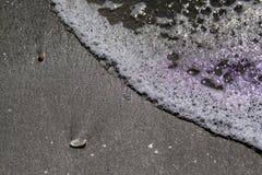 Espuma de la onda en la arena imagen de archivo