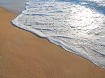 Espuma del océano en una playa arenosa Foto de archivo
