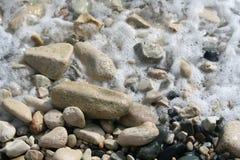 Espuma do mar nos seixos da praia fotografia de stock