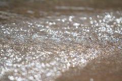 A espuma e a areia borbulhantes do mar na praia Fotografia de Stock