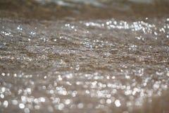 A espuma e a areia borbulhantes do mar na praia Foto de Stock