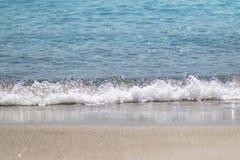 A espuma e a areia borbulhantes do mar na praia Imagem de Stock